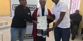 Rosond giving Project Manager, Thandi Ngaloshe, the car ownership document.